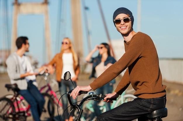 親友との素晴らしい一日。カメラを見て、彼の友人がバックグラウンドで話している間笑顔で自転車に乗ってハンサムな若い男