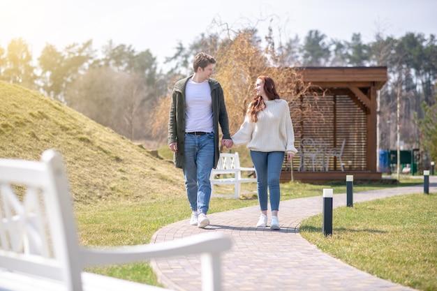 素晴らしい日。自然の中を歩いてお互いを見つめながら手をつないでカジュアルな服を着て笑顔の若い大人の男と女
