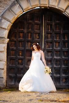 素晴らしいイベント、ウェディングブーケのコンセプト。木製のドアの上の葉、バラ、蘭の花、芽の花束を持って花嫁。豪華なアクセサリー。パステルカラー。クラシックなレトロなスタイル。室内撮影