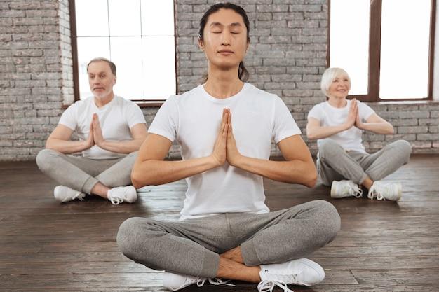 素晴らしい例です。インストラクターの後ろに座って瞑想しようとしている胸の前で手をつないでいる退職の喜びのカップル