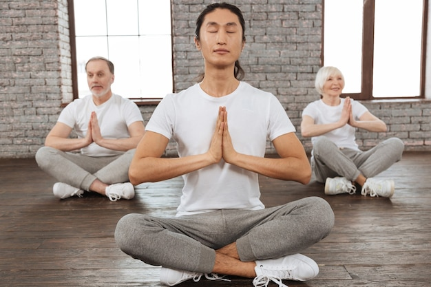 Great example. delighted couple of retirements holding hands together in front of the chest trying to meditate while sitting behind their instructor