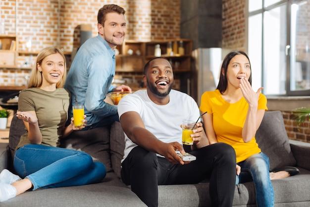 Великий фильм. четыре возбужденных счастливых привлекательных друга расслабляются, смеясь и смотря фильм