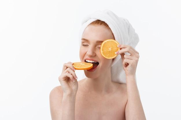 健康的なライフスタイルのための素晴らしい食べ物。オレンジの部分を保持している美しい若い上半身裸の女性