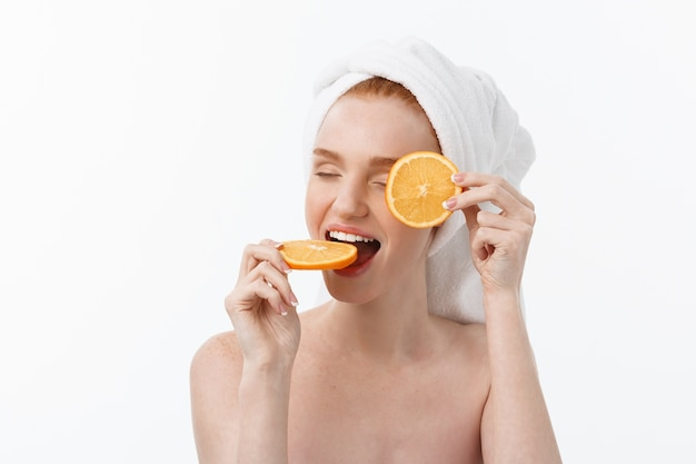 Great food for a healthy lifestyle. beautiful young shirtless woman holding piece of orange
