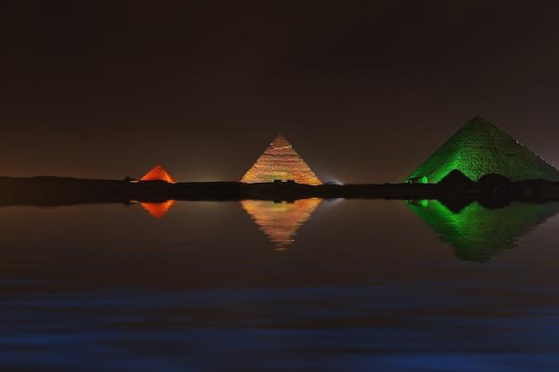 Great giza pyramids at night, water reflection.