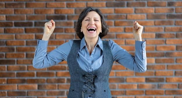 Отличная концепция хороших новостей. портрет завербованной красивой счастливой пожилой женщины в деловой одежде