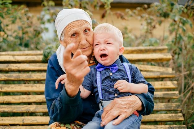 Прабабушка держит правнука на коленях на улице.