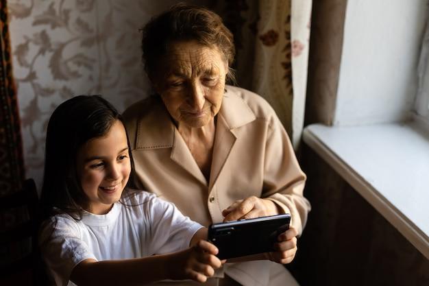 曽祖母は曽孫娘と一緒に座ってスマートフォンを覗き込みます。祖母と子供がスマートフォンで自分撮りをします。孫娘と一緒の祖母が電話を調べます。