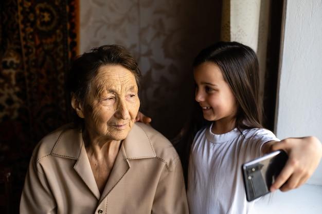 Прабабушка сидит с правнучкой и смотрит в смартфон. бабушка и ребенок делают селфи на смартфоне. бабушка с внучкой заглядывают в телефон.