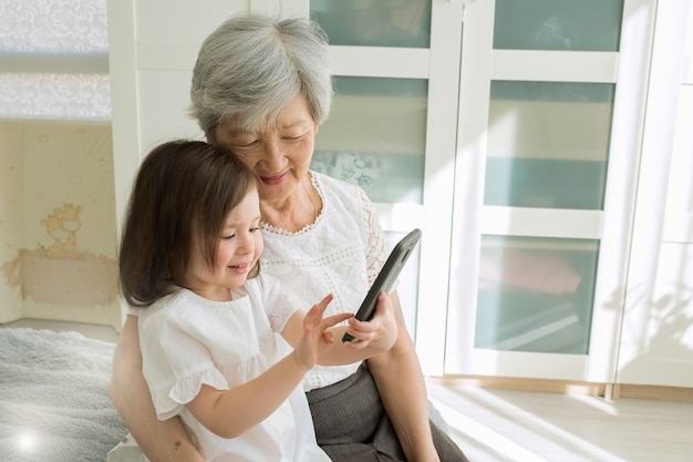 Great-grandmother sits with great-granddaughter and looks into the smartphone.
