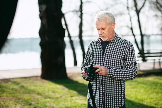素晴らしい趣味。屋外に立ってカメラを使用して物思いにふける年配の男性