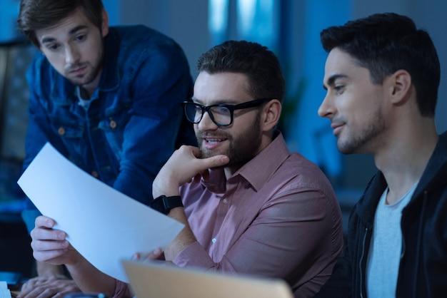 Отличная идея. радостный позитивный бородатый мужчина держит подбородок и улыбается, беря лист бумаги