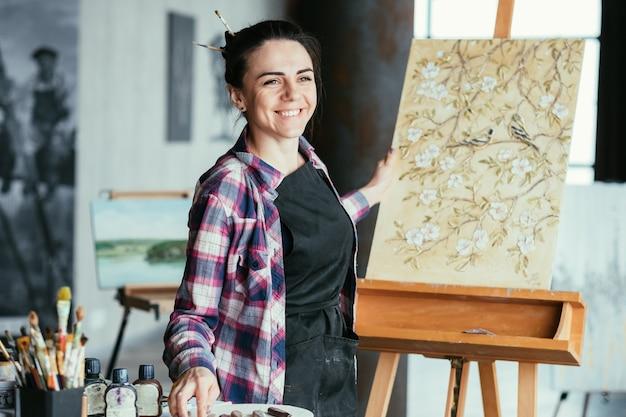 いい案。幸せな思い出と喜び。仮想オブジェクトでイーゼルに絵を描く笑顔の女性アーティスト。アートワークルーム。