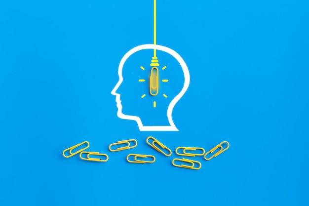 Концепция великих идей с человеческим мозгом, скрепкой, мышлением, творчеством, лампочкой на синем фоне, новой концепцией идей