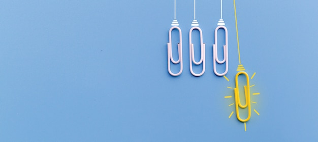 Great ideas concept with paperclip thinking creativity light bulb on blue background