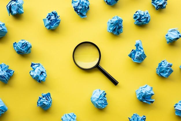虫眼鏡と紙のしわくちゃのボールの色の背景と素晴らしいアイデアの概念。