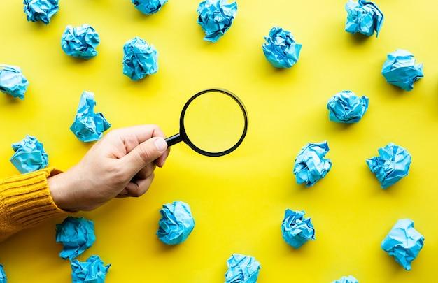 종이 구겨진 공 색 배경을 찾고 돋보기를 사용하여 남성 손으로 훌륭한 아이디어 개념