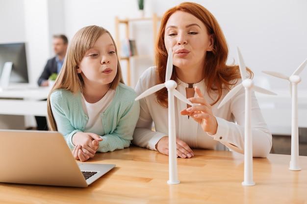 풍력 터빈이 작동하는 방식을 자녀에게 설명하는 훌륭한 영감을받은 특별한 엄마