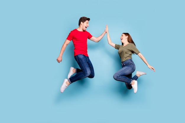 잘 했어! 쾌활한 두 낭만적 인 사람 점프의 전체 길이 프로필 측면 사진 하이 파이브 축하 승리 착용 현대 티셔츠 데님 청바지 운동화 격리 된 파란색 배경