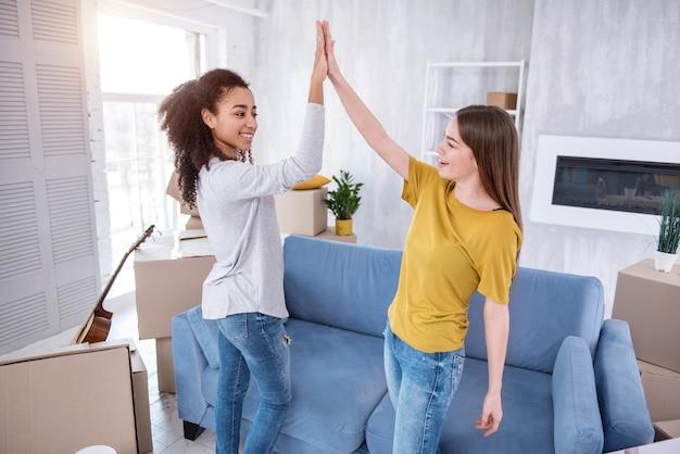 Прекрасная работа. жизнерадостные молодые девушки дают друг другу высокую оценку после распаковки значительного количества коробок с вещами.