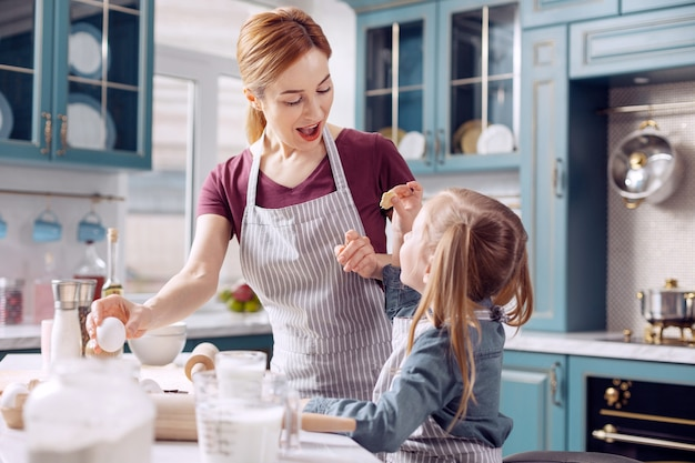 Great job. upbeat young woman in an apron looking at a small cookie in her daughters hands with excitement, praising her for good job, while making dough