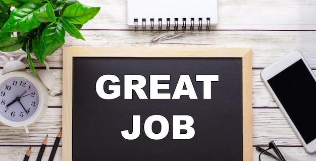 Отличная работа, написанная рядом с карандашами, смартфоном, белым блокнотом и зеленым растением в горшке