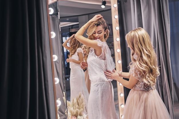 멋져 보여! 피팅 룸에 서 있는 동안 그녀의 여자 친구에 드레스를 조정 하는 젊은 아름 다운 여자