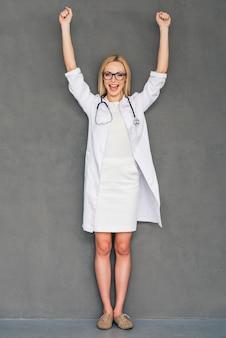 훌륭한 의료 결과! 아름다운 젊은 여성 의사가 머리 위로 손을 얹고 회색 배경에 서서 미소를 지으며 카메라를 바라보고 있습니다.