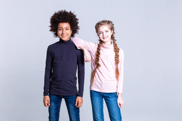 In great mood. beaming long-haired girl with two braids leaning on shoulder of her african american positive friend