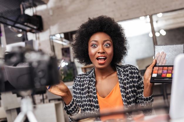 Отличное настроение. красивая темнокожая женщина с кудрявыми волосами выглядит возбужденной, проводя онлайн-урок о моде