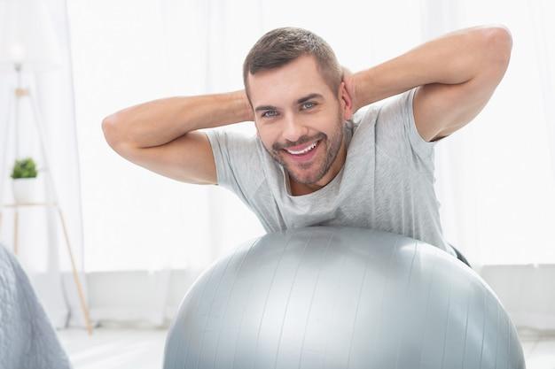 Отличное настроение. веселый счастливый человек смотрит на вас во время тренировки в медицинском мяче