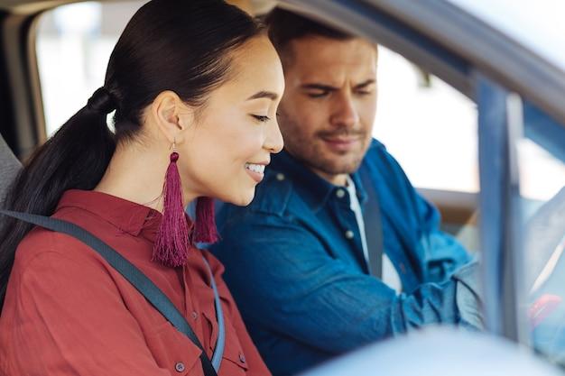 素晴らしい気分。彼女のボーイフレンドと一緒に車に座って笑っている喜んで陽気な女性