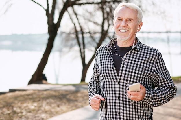 Отличное настроение. энергичный старший мужчина гуляет и наслаждается музыкой