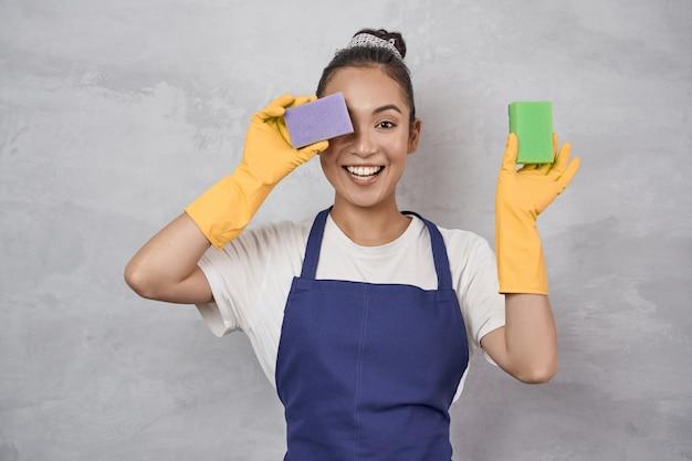制服を着たおかしな掃除婦と片目を覆うゴム手袋を掃除するのに最適な気分