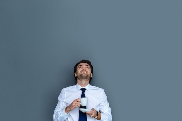 素晴らしい気分。コーヒーを飲みながらオフィスで働いている間見上げるうれしそうなひげを生やしたポジティブな男
