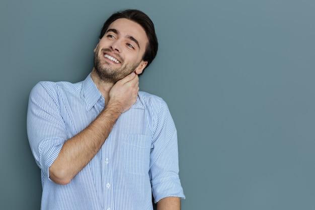 素晴らしい気分。首に触れて前向きな気分で笑っているうれしそうな素敵な前向きな男
