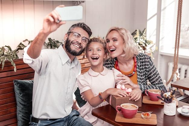 좋은 분위기. 사진을 위해 포즈를 취하는 동안 테이블에 함께 앉아 즐거운 긍정적 인 가족