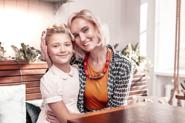 Отличное настроение. радостные позитивные мать и дочь улыбаются вам, сидя вместе