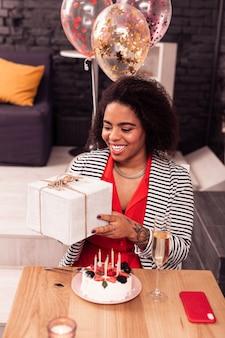 Отличное настроение. радостная позитивная женщина, держащая подарочную коробку, сидя перед тортом