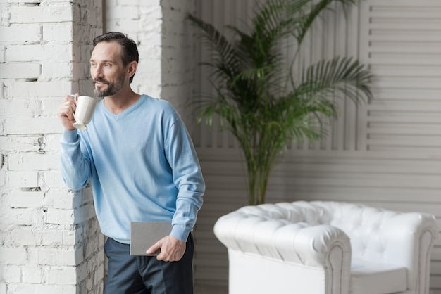 Great mood. nice optimistic happy man holding a notebook and drinking coffee while having a good mood
