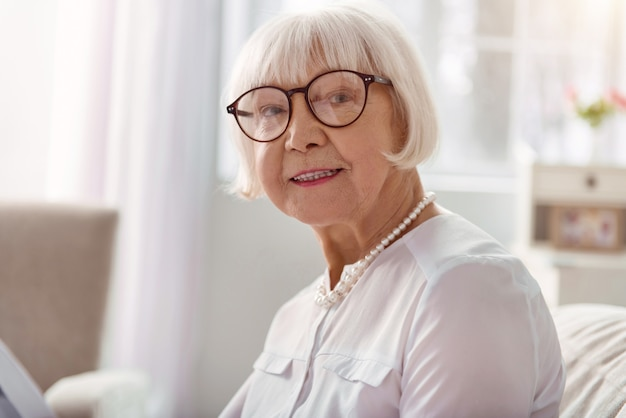 素晴らしい気分。ソファに座って笑っている眼鏡で楽しいうれしそうなシニア女性のクローズアップ