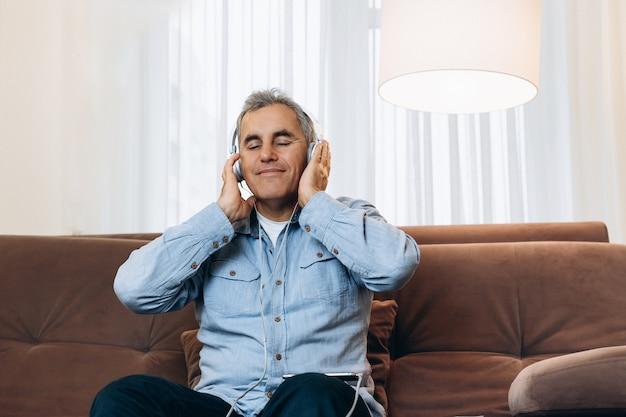 素晴らしい音楽!中年男性は茶色のソファに座り、両手でヘッドホンを持ち、好きな音楽を楽しんでいます。背景に居心地の良いリビングルーム。スマートフォンを使用して笑顔でカジュアルウェアの男性。