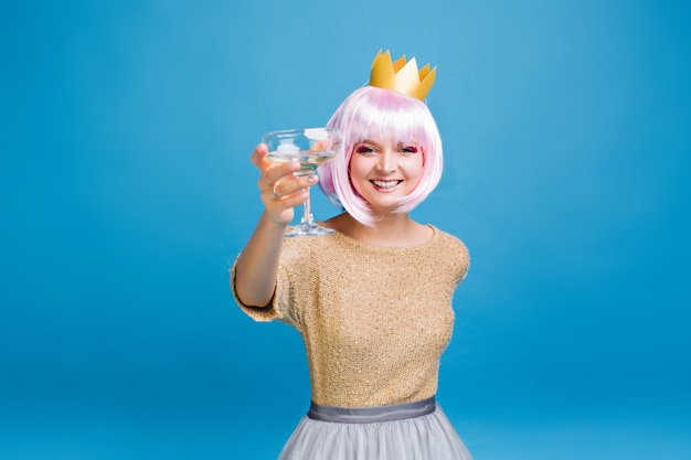 Great new year party celebration of joyful young woman with cut pink hair in golden crown . fashionable model, drinking champagne, party time, birthday, smiling.