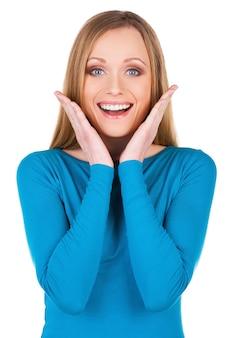 Отличные новости! красивая молодая улыбающаяся женщина смотрит в камеру и жестикулирует, стоя изолированной на белом