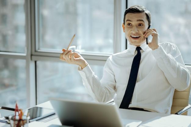 素晴らしいニュース。彼のオフィスのテーブルに座って、広く笑っている魅力的な若い男は、電話で話している間、良いニュースにうれしく驚いています