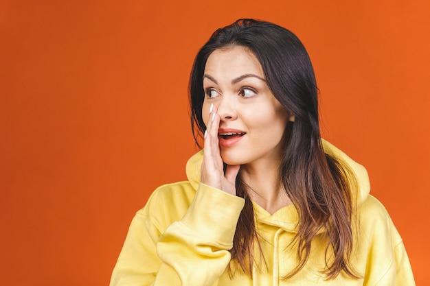 좋은 소식! 오렌지 배경에 비밀을 말하고 쾌활 한 행복 예쁜 여자.