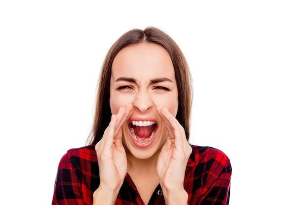 素晴らしいニュース!口の近くで手をつないで叫んで陽気な若い女性