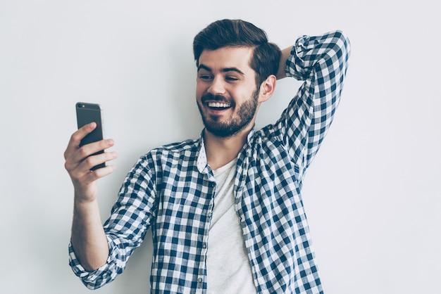 友人からの素晴らしいニュース。スマートフォンを持って笑顔でそれを見て幸せな若い男