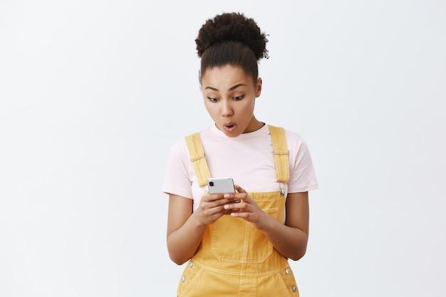 私の友人からの素晴らしいニュース。トレンディな黄色のオーバーオール、スマートフォンを持って、画面にメッセージを録音し、驚いてデバイスを見つめている、驚きと興奮の美しいアフリカ系アメリカ人を喜ばせます