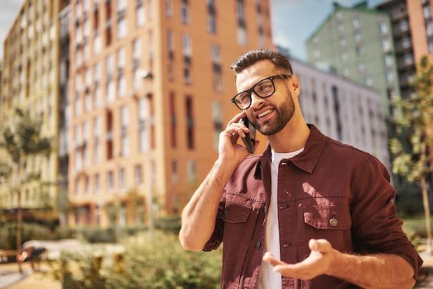 素晴らしいニュースカジュアルな服装と眼鏡をかけた幸せなひげを生やした男性が電話で話し、通りに立って笑っています。ライフスタイル。デジタル。コミュニケーション
